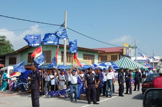 Tarian Angkuh oleh perayu undi Barisan Nasional sambil diawasi oleh beberapa orang anggota polis
